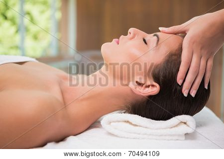 Side view of an attractive young woman receiving head massage at spa center