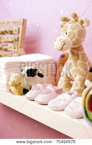 Stuffed toys, shoes and nappies on shelf in baby's room