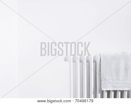 Towel on radiator and white wall