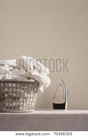 Iron next to laundry basket on table