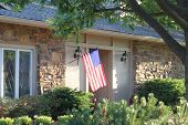 picture of nice house  - A nice house with a large American flag - JPG