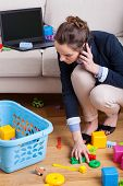 pic of toy phone  - Businesswoman talking on phone and picking up toys - JPG