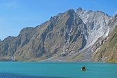 picture of canoe boat man  - A man explores gorgeous Lake Pinatubo by boat - JPG