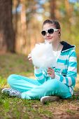 picture of candy cotton  - Smiling happy girl in sportswear in spring park eating cotton candy - JPG