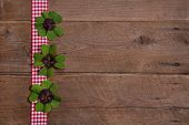 foto of red clover  - Wooden background with red and white checkered ribbon and green clovers for a happy new year - JPG