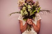 stock photo of condolence  - A young woman is holding a bouquet of dead flowers - JPG