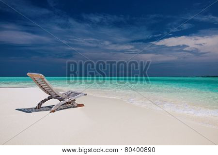 Beach view of amazing water in Maldives - empty chair on sand