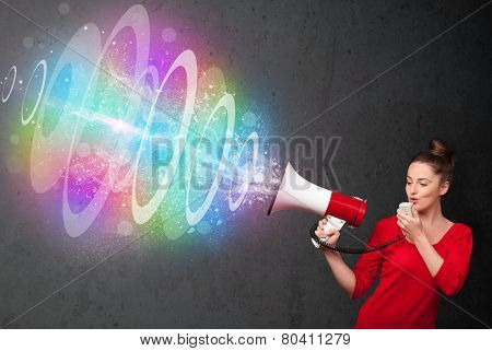 Cute young girl yells into a loudspeaker and colorful energy beam comes out
