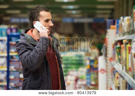 Handsome Man On Mobile Phone At Supermarket