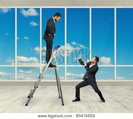 displeased businessman looking down at man in fighting stance. photo in room with big window