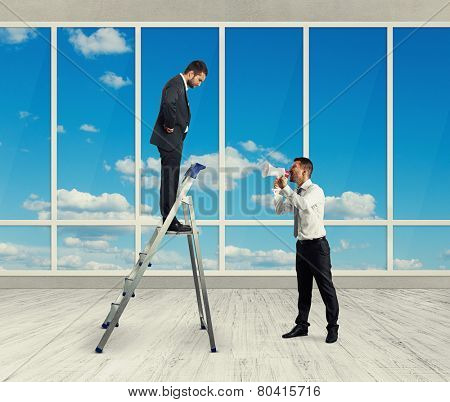 serious businessman standing on the stepladder and looking down at screaming man with megaphone. photo in room with big windows