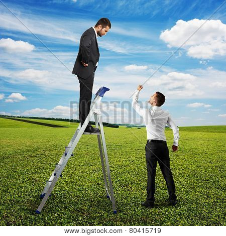 angry screaming man looking at man on the stepladder and showing his fist. photo at outdoor