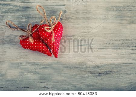 Valentines day. Red cloth handmade hearts on wooden background.