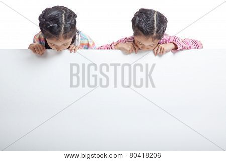 Asian twin sisters behind empty billboard look at the billboard