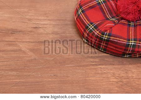 Traditional Scottish Red Tartan Bonnet On Wood Board