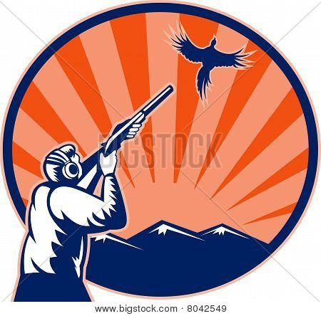 Hunter aiming shotgun rifle at bird pheasant