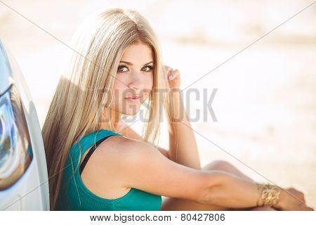 Bright woman - blonde, near white car.