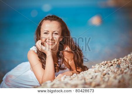 A woman in a light summer dress relaxing on the beach.