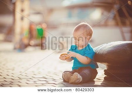 Little girl sitting on a pier on the background of ships.