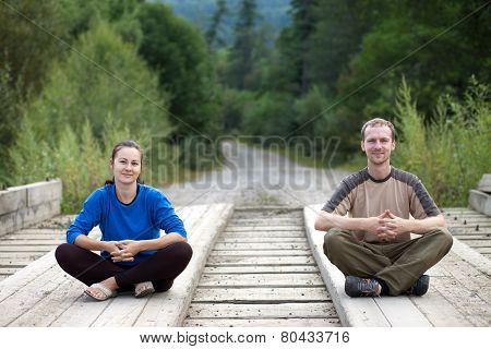 Tourist Couple Sitting On A Wooden Bridge