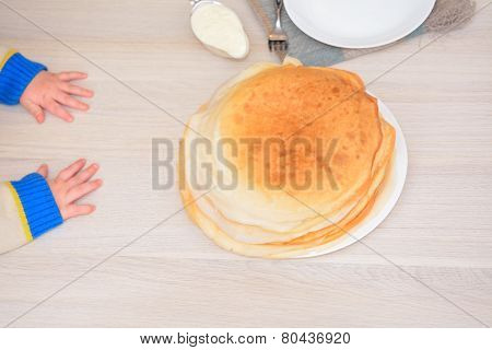 Toddler's Hands On The Table Next To The Stack Of Pancakes