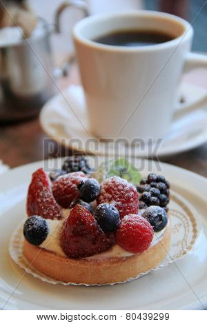 Fresh fruit tart and hot cup of coffee