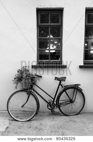 Old, rusty bicycle leaning against wall