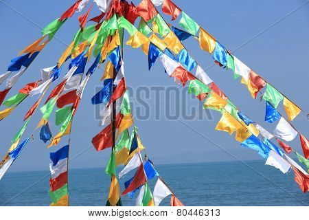 buddhist tibetan prayer flags waving in the wind against blue sky