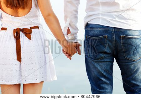 Happy Couple In Love Holding Hands Near The Sea