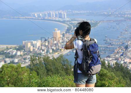 woman hiker taking photo at seaside mountain peak