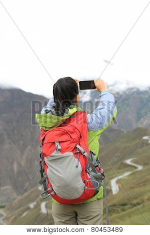 woman hiker taking photo of nujiang river 72 turn road, tibet,china