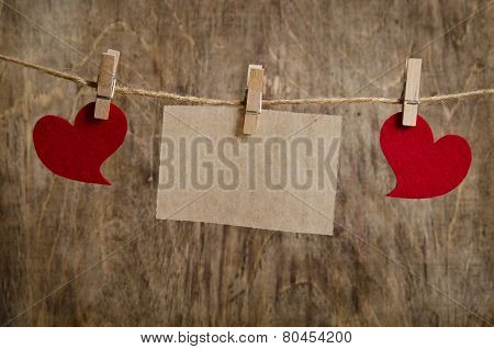 Two Red Fabric Hearts With Sheet Of Paper Hanging On The Clothesline On Three Clothespins . On Old W