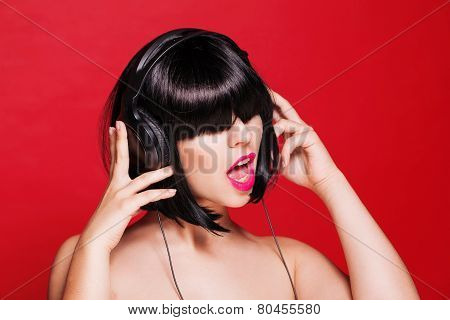 Woman listening to music on headphones enjoying a dance. Closeup portrait of beautiful girl with pin
