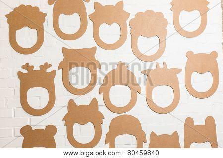 Set Of Cardboard Masks On A White Brick Wall.