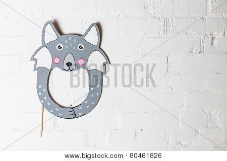 Bright Cardboard Mask On A White Brick Wall.