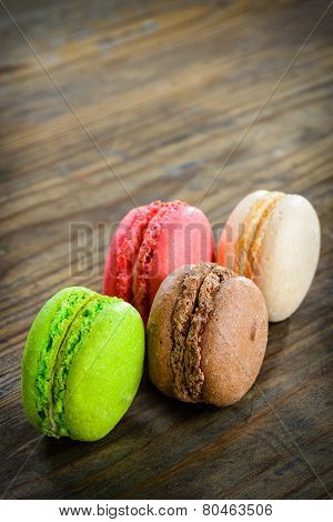 Different kinds of macaroons in stack on wooden background, selective focus