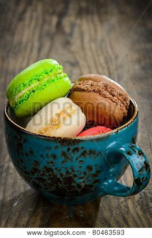 Sweet and colourful french macaroons on wooden background