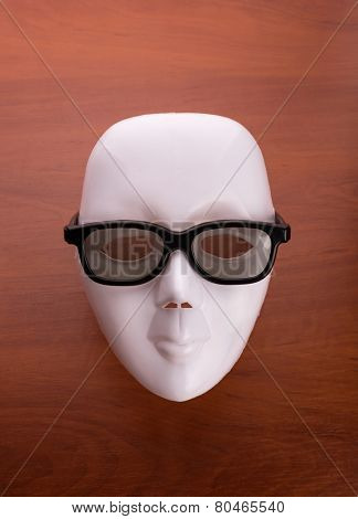 Theater mask in glasses on the table