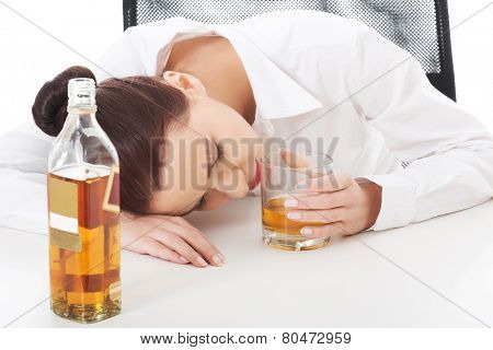 Alone young businesswoman in depression, drinking alcohol.
