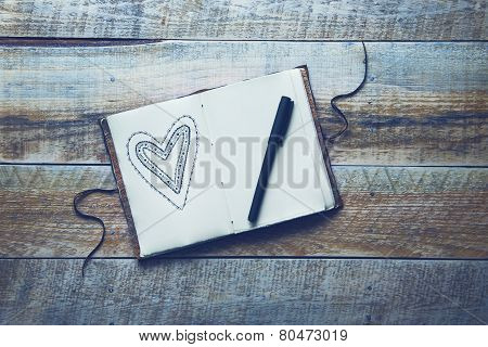 Old Paper Sketch Book With Hand-drown Heart Over Vintage Wooden Background