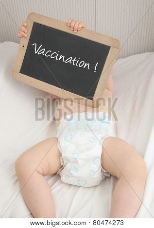 Baby with blackboard written Vaccination