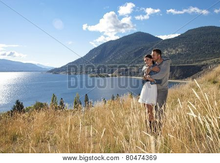 Outdoor photo of young couple embracing in grassy field at scenic viewpoint