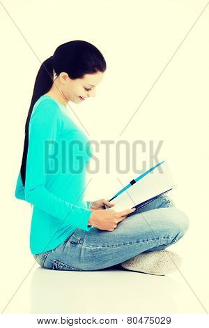 Beautiful young woman student sitting with workbook.