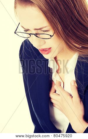 Beautiful business woman touching her chest, feeling unwell. Heart attack, health concept.
