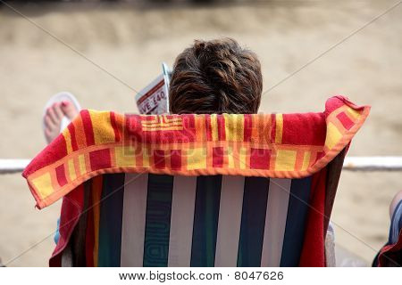 Woman Reading Magazine Whilst Relaxing In Deckchair