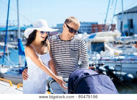 Young and attractive couple walking with a baby pram outdoor