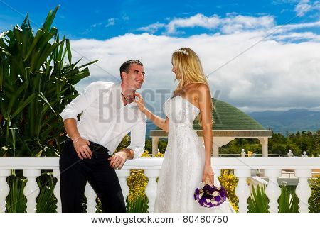 Happy Bride And Groom Standing Next To The Stone Gazebo Amid Beautiful Tropical Landscape.