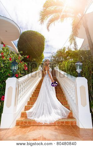 Beautiful Bride In Wedding Dress With Long Train Standing On The Stairs In The Hotel