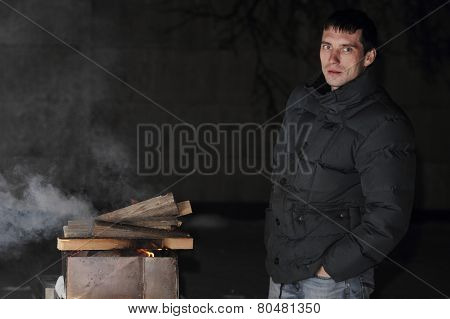 man grilling at night with a fire that's too big.