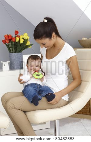 Pretty young mother holding baby boy on lap. Baby playing with toy.